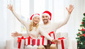 Happy couple at home with christmas gift boxes holidays and people concept in santa hats sitting on sofa Stock Images