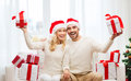 Happy couple at home with christmas gift boxes holidays and people concept in santa hats sitting on sofa Stock Photography