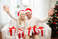 Happy couple at home with christmas gift boxes holidays and people concept in santa hats sitting on sofa Stock Photo