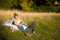 Happy couple hugging and lying in the grass on background forest Royalty Free Stock Photo