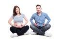 Happy couple with joyful husband standing like his pregnant wife