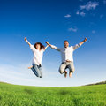 Happy couple jumping in green field against blue sky summer vacation concept Stock Photography