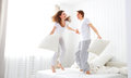 Happy couple jumping and having fun in bed Royalty Free Stock Photo