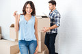 Happy couple with key and boxes moving to new home Royalty Free Stock Photo
