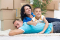 Happy couple with a kid in their new home laying on the floor cardboard boxes around Royalty Free Stock Photos