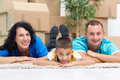 Happy couple with a kid in their new home laying on the floor wi Royalty Free Stock Photo