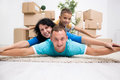 Happy couple with a kid in their new home laying on the floor wi Stock Photos