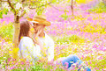 Happy couple kissing outdoors young family having fun on floral field spending time together in summer garden love concept Royalty Free Stock Photos