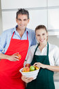 Happy couple in kitchen with fruit standing bowl of Royalty Free Stock Photos