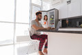 Happy Couple On Kitchen Using Laptop Computer Modern Apartment With Panoramic Window Royalty Free Stock Photo