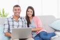 Happy couple with laptop on sofa Royalty Free Stock Photo