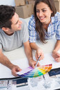 Happy couple looking at a color chart to decorate their house new Stock Images