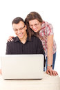 Happy couple looking at laptop smiling with glasses white with joy Royalty Free Stock Photography
