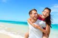 Happy couple in love on beach summer vacations joyful asian girl piggybacking young caucasian boyfriend playing and having fun Royalty Free Stock Images
