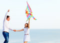 Happy couple in love with flying a kite on the beach young Stock Photography