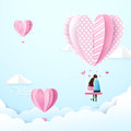 Happy couple in love swings with heart shape balloons in the air