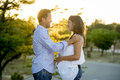 Happy couple in love together in park landscape on sunset with woman pregnant belly and man Royalty Free Stock Photo