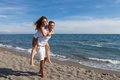 Happy couple in love walking on the beach Royalty Free Stock Photo