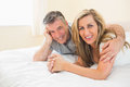 Happy couple lying on a bed looking at camera in bedroom Royalty Free Stock Images