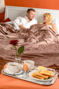 Happy couple lying bed romantic breakfast hotel Royalty Free Stock Image