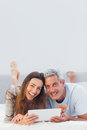 Happy couple lying on bed using their tablet pc in bedroom Stock Photo