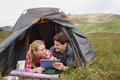 Happy couple lying in their tent and using digital tablet the countryside Royalty Free Stock Image