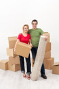 Happy couple moving together carrying their stuff Stock Image