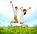 Happy couple outdoor jumping family on green field Royalty Free Stock Photo