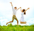 Happy couple outdoor jumping family on green field Royalty Free Stock Photography
