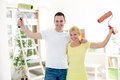 Happy couple painting holding raised paint roller concept apartment Royalty Free Stock Photos