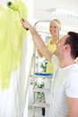 Happy couple painting young in their new apartment Stock Photography