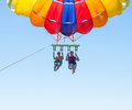 Happy couple Parasailing in Dominicana beach in summer. Couple under parachute hanging mid air. Having fun. Tropical Paradise. Pos Royalty Free Stock Photo