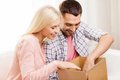 Happy couple with parcel box at home people delivery shipping and postal service concept opening cardboard or Royalty Free Stock Images