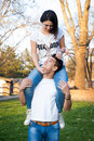 Happy couple in a park love having fun girl sitting at boy s shoulders Royalty Free Stock Photo