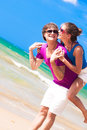 Happy couple piggybacking cheerful on beach on Stock Image