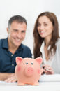 Happy couple with piggybank in front of defocused Stock Photo