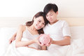 Happy couple with pink piggy bank young lying in a bed asian family Stock Photos