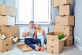 Happy couple with pizza in a new apartment for a housewarming. Royalty Free Stock Photo