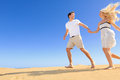 Happy couple in playful and romantic relationship having fun under sun blue sky desert two young lovers running cheerful Stock Image