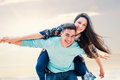 Happy couple playing around outdoors close up portrait of teen boy piggybacking girlfriend Stock Image