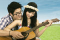 Happy couple playing guitar portrait of at the park Royalty Free Stock Images