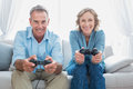 Happy couple playing video games together on the couch at home in living room Stock Photos