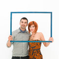 Happy couple posing through a frame young caucasian an empty on white background Royalty Free Stock Photo
