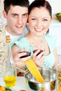 Happy couple preparing spaghetti and drinking wine Royalty Free Stock Images
