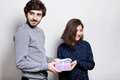 A happy couple with present. A hipster guy presenting a gift to his girlfriend looking aside. Young male and female isolated over Royalty Free Stock Photo