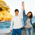 Happy couple raising arms at seaside. Royalty Free Stock Photos