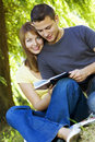 Happy couple reading a book outdoors Royalty Free Stock Image