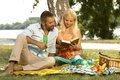 Happy couple reading book together at picnic casual outdoor attractive caucasian blonde woman handsome man basket cloth smiling Royalty Free Stock Image