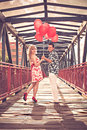 Happy couple with red balloons on the bridge young Stock Images