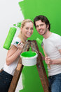 Happy couple redecorating their new house standing on a wooden stepladder painting the wall a bright green and smiling at the Royalty Free Stock Photos